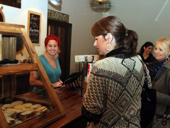 Alex Root, left, manager of Miss Lucille's, takes lunch