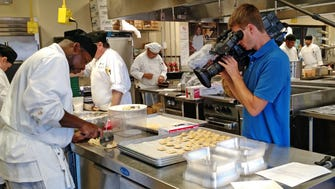 Brian Ewig films a student at work in a culinary arts class at Milwaukee Area Technical College for a Milwaukee PBS television series about the program.