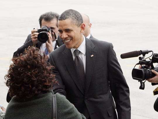 President Barack Obama greets people at JFK International Airport in New York in 2011. Behind him photographing the action is Pete Souza.