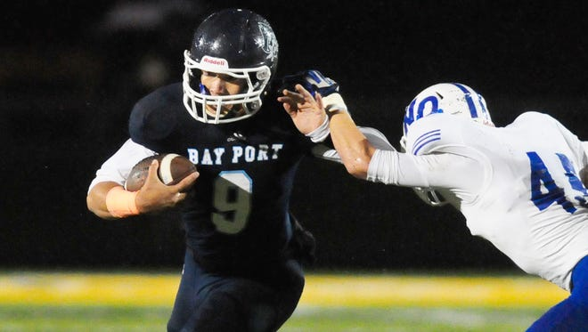 Bay Port quarterback Alec Ingold gets past Notre Dame Academy's Kyle Blindauer on a first-quarter run in an FRCC game played at Goelz Field in Ashwaubenon, Friday, September 12, 2014.