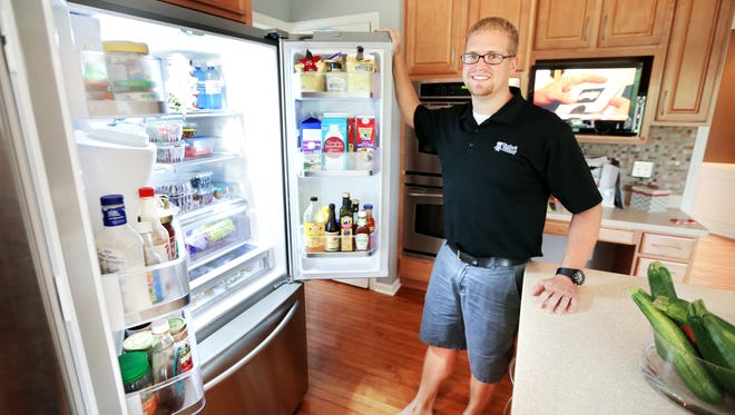 Matt Allen, fourth generation co-owner of Taylor's Bakery out of Indianapolis, stands with his refrigerator and its contents as we take a look at whats inside on Thursday, August 21, 2014.