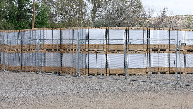 Stacks of photovoltaic modules for a planned solar far sit in an empty lot on Saturday at the end of South Drake Avenue between West Pinon Street and West Murray Drive.