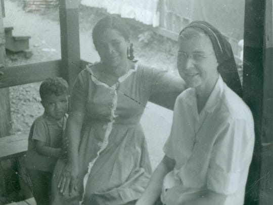 Sister Ann Jude Van Lanen (far right) visits with a Nicaraguan woman and boy.