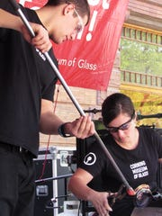 Corning Museum of Glass employees Tom Ryder and Jamie Perian apply molten glass to a decorative glass fish during Sunday's hot glass show at GlassFest.