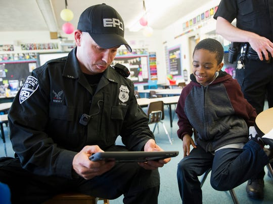 Evansville Police Officer Craig Pierce, left, plays a video game with Dexter Elementary School first grader, De'Andre Fellows, 7, on Thursday.