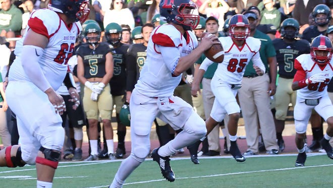 Dixie State University quarterback Blake Barney, center, set a school-record 291 yards and three touchdowns in a game against South Dakota School of Mines Saturday, Oct. 31, 2015.