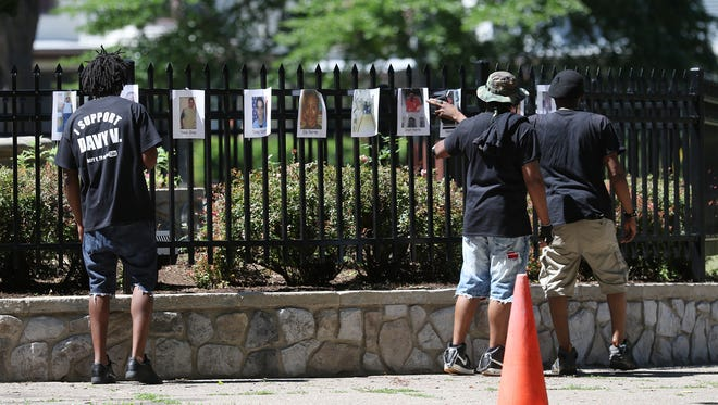 """Quin Bostick, Fahiym Yahbless and YahSon Izrealmos, with The Black Panther Party of Rochester look over the photos of homicide victims at Roc the Peace Festival held at Jones Square Park.  Yahbless said there were """"a lot of faces we recognize, this is terrible.""""  The group came out to support the event."""