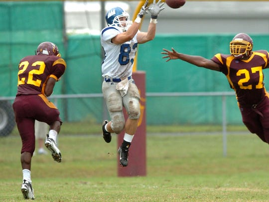 Christopher Newport's Michael Dorn leaps to make a reception between Salisbury's Byron Westbrook (22) and Michael Hatcher (27) during the second half of a 2006 game in Salisbury