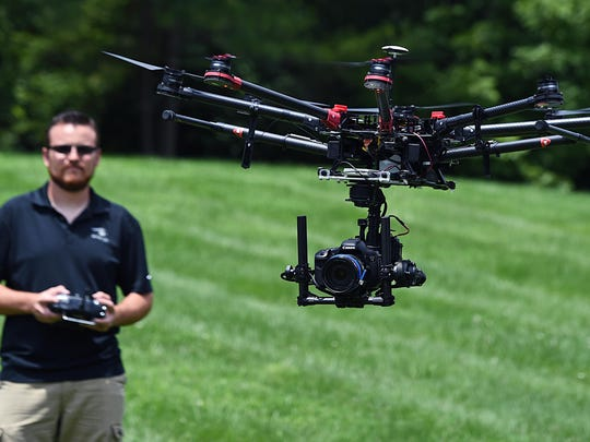 SnapRoll Media co-founder and pilot Spencer Valdez demonstrates flying an unmanned aerial vehicle outside the company's headquarters in Franklin on July 11, 2015. The aerial videography production company has been approved by the FAA to fly for commercial movie and TV production.