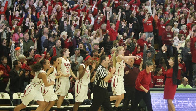 The CVU bench and fans celebrate as the buzzer sounds on the Redhawks' 35-34 victory over Rice in the Division I championship game at Patrick Gymnasium in March.