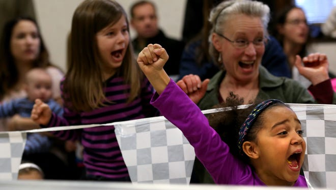 Meya Johnstone cheers on a fellow Daisies car during the Irondequoit girl scouts first Pinewood Derby. Boy Scout Troop 203 donated time, equipment, and services to help run the event.