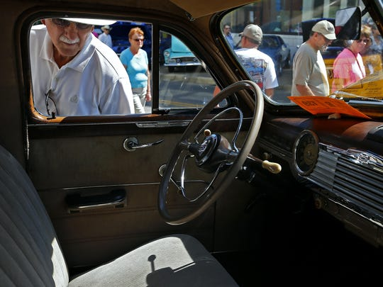 Carl Boswell peers into a 1947 Chevy owned by Jerry