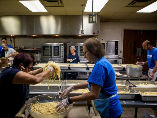 Maria Trester adds pasta to pans with Mary Morgan,