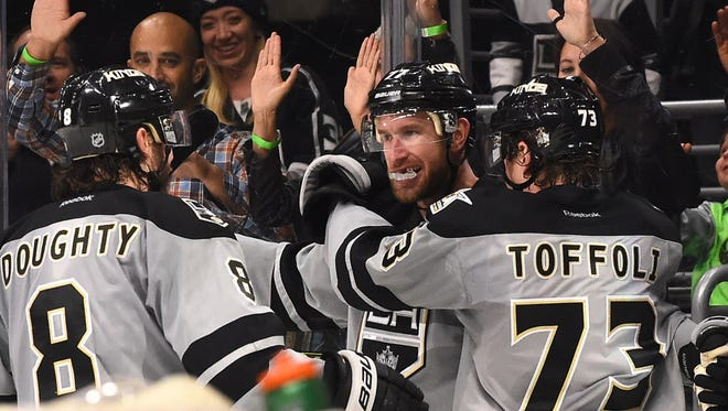 Kings defenseman Drew Doughty (8) and forward Tyler Toffoli (73) celebrate with Jeff Carter (77) after his game-winning goal in overtime against the Blackhawks.