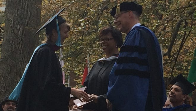 A student receives her diploma from Earlham College.