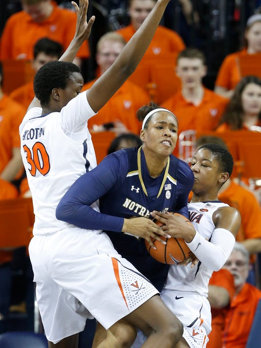 Notre Dame forward Kristina Nelson (21) tries to get away from Virginia guard Dominique Toussaint, right, and Virginia center Felicia Aiyeotan (30) during the first half of an NCAA college basketball game in Charlottesville, Va., Thursday, Feb. 15, 2018. (AP Photo/Steve Helber)