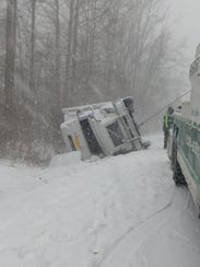 An overturned tractor trailer sits alongside I-84 in