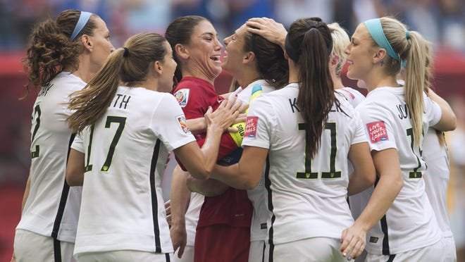 United States' Carli Lloyd, center, is mobbed by teammates as she celebrates her third goal against Japan during the first half of the FIFA Women's World Cup soccer championship in Vancouver, British Columbia.