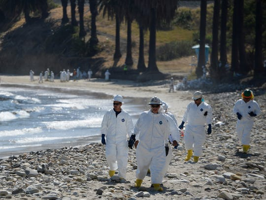 Workers walk along Refugio Beach as efforts continue