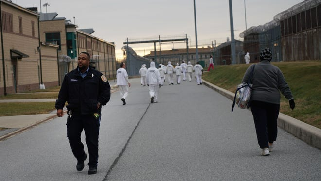 A correctional officer walks past inmates at the James T. Vaughn Correctional Center as they move between buildings.