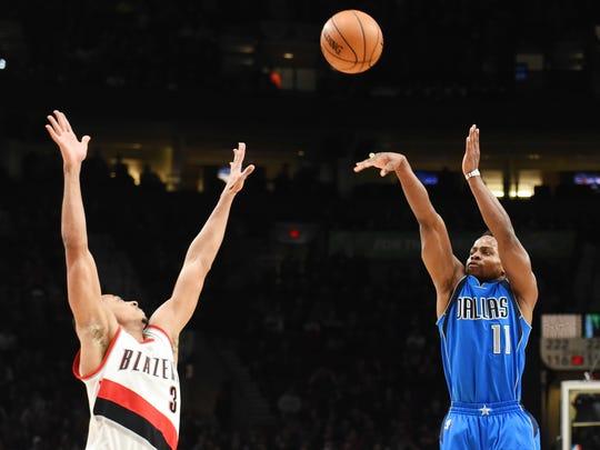 Dallas Mavericks guard Yogi Ferrell shoots and hits a shot over Portland Trail Blazers guard C.J. McCollum (3) during the first quarter of the game at the Moda Center.