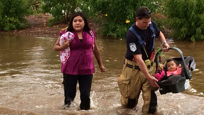 Firefighters aid in the rescue of children from a Chandler day-care center surrounded by water near Dobson Road and Chandler Boulevard on Monday, Sept. 8, 2014. The day-care center closed due to the flooding, and firefighters showed up to assist in the pick-up of children.
