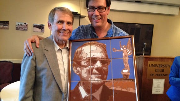 "State Sen. Steve Farley presents longtime House policy adviser Mark Bogart with a portrait done with Farley's ""tilography"" art technique."