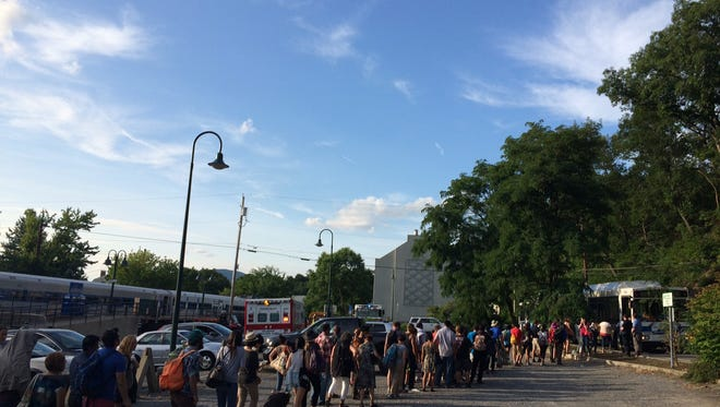Passengers wait to board buses that will take them from Garrison south to Peekskill, where they can re-board trains to New York City. A rock slide took out all train tracks in the area of Garrison July 19, 2014.