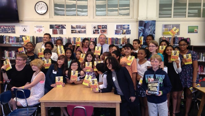 """James Patterson visits with students from Manhattan's Community East Side School to donate a copy of his book, """"Middle School: The Worst Years of My Life,"""" to every member of the class."""