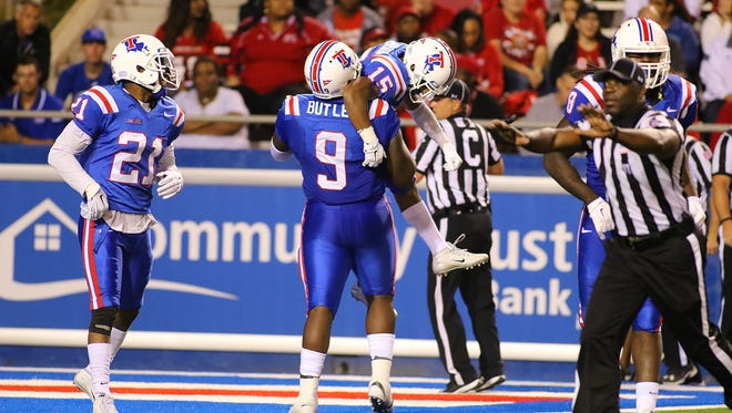 Louisiana Tech defensive tackle Vernon Butler (9) hoists up Bryson Abraham (15) after he returned an interception for a touchdown in Saturday's win over UL Lafayette.