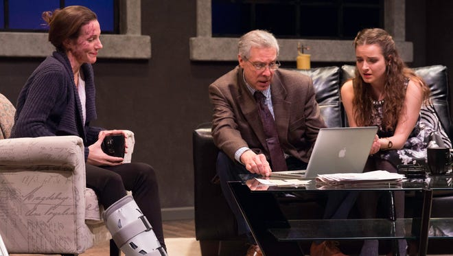 """Kay Allmand (left) looks on while Richard Ganoung and Jordan Watson fret over a screen in """"Time Stands Still."""""""