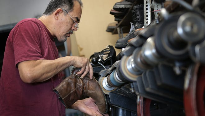 Javier Rodriguez scuffs the bottom of a boot before applying glue as he resoled the boots Friday at Texas Boot and Shoe Repair at 10781 Pebble Hills.
