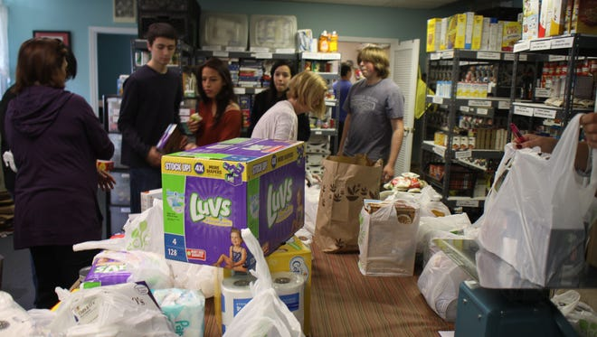 Ridgewood Volunteers and teens from the GR & RW Interact clubs help sort and shelve food at the food bank by the train station.