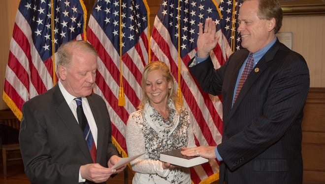 With his wife holding the Bible, Matt Holt is sworn in as Hunterdon County freeholder director by Congressman Leonard Lance.