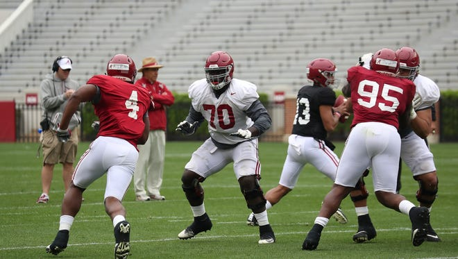 Alabama sophomore offensive tackle Alex Leatherwood (70) prepares to block sophomore outside linebacker Christopher Allen (4) while teammates Jedrick Wills Jr. and Johnny Dwight (95) are locked up in front of sophomore quarterback Tua Tagovailoa (13) during Saturday's spring scrimmage from Bryant-Denny Stadium in Tuscaloosa, Ala. (Photo courtesy of Alabama athletics)