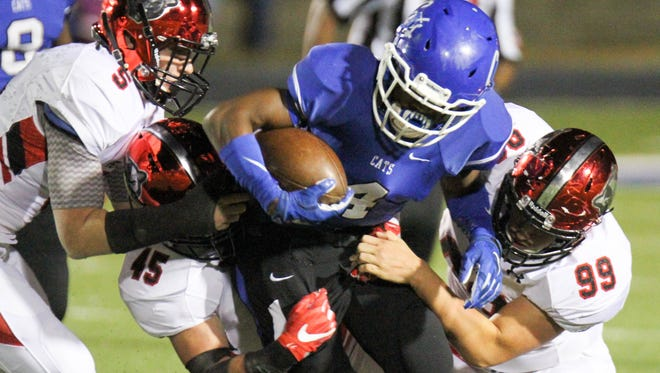 Meridian's Jaquaris Dean fights for yards as he's wrapped up by Petal defenders on Friday.