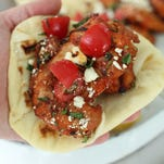 Grilled gochujang chicken thighs with feta and fresh mint served up in a roll.