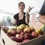 Julie Abbott, St. Matthews Area Ministries executive director, helps sort through fresh produce during a Tuesday morning food distribution at Beechwood Baptist Church. The program has been displaced by a recent flood in the basement of the church and forced to operate outdoors.