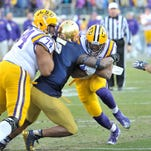 LSU Tigers quarterback Anthony Jennings (10) rushes against the Notre Dame Fighting Irish linebacker Nyles Morgan (5) as teammate LSU offensive tackle Vadal Alexander (74) attempts to block during the first half at LP Field.