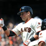 May 31, 2015; San Francisco, CA, USA; San Francisco Giants second baseman Joe Panik (12) is greeted at home plate after hitting a RBI home run against the Atlanta Braves in the seventh inning of their MLB baseball game at AT&T Park. Mandatory Credit: Lance Iversen-USA TODAY Sports