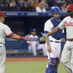 Philadelphia Phillies' Ryan Howard, right, is congratulated by teammate Carlos Ruiz after hitting a solo home run, as Toronto Blue Jays catcher Josh Thole watches during the seventh inning of a baseball game Monday, June 13, 2016, in Toronto. (Chris Young/The Canadian Press via AP)