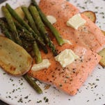 Baked steelhead trout is paired with asparagus, potatoes and herbs.