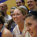 Lauren Hill, center,  poses for a photo with her teammates