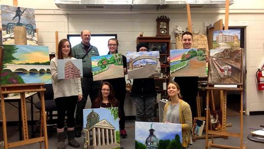 SUNY-Broome Art and Design students and Professor Hall Groat show off several of the paintings in the exhibit.
