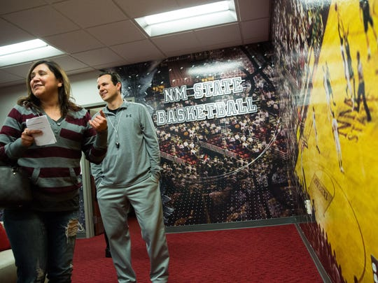 New Mexico State men's basketball coach Paul Weir, talks with Danielle Gibbs, who spotted herself and her family in the large photo on the wall of the offices of the basketball staff, Tuesday during the Aggies Basketball Women's Clinic at NMSU.