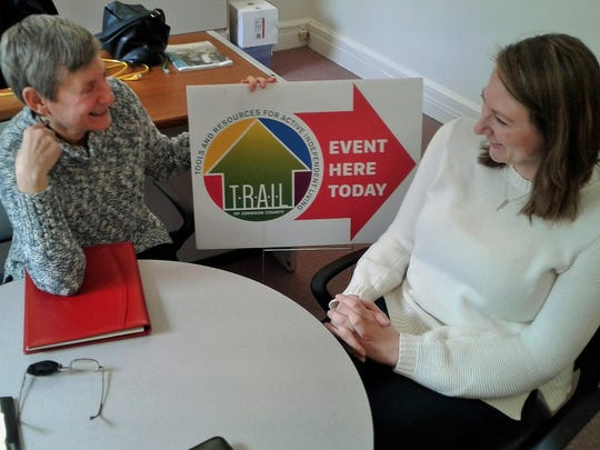The TRAIL logo on this event sign is cropping up more in Johnson County.  Susan Shullaw, left, and Hillary Ramaker discuss ways this new, volunteer-based nonprofit works to help keep older residents in their own homes.