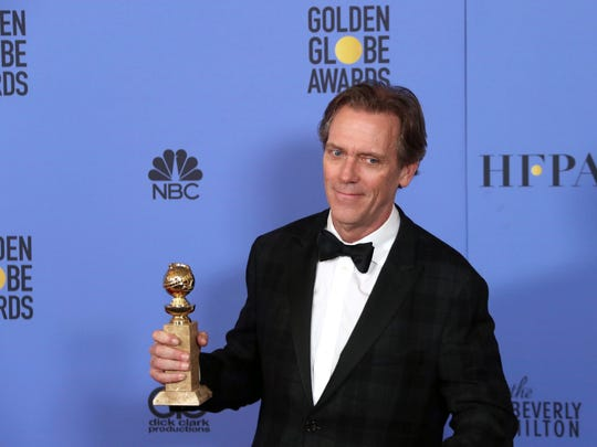 Hugh Laurie holds his award for TV supporting actor (for 'The Night Manager') at the Golden Globes.