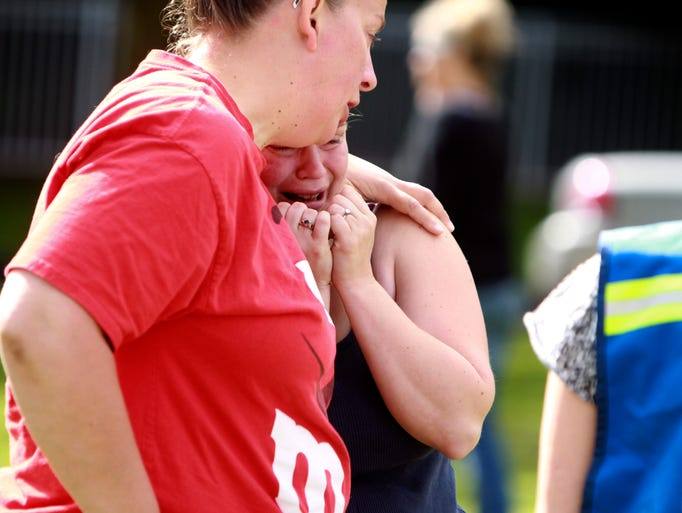 Women comfort each other after a shooting at Reynolds High School on June 10 in Troutdale, Ore. A gunman shot and killed a student at the school shortly after classes began and was found dead as police arrived.