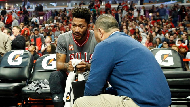 Chicago Bulls guard Derrick Rose (left) talks with Chicago Bulls head athletic trainer Jeff Tanaka after he sprained his left ankle during the second half of an NBA game against the Indiana Pacers at United Center on Nov. 16, 2015.
