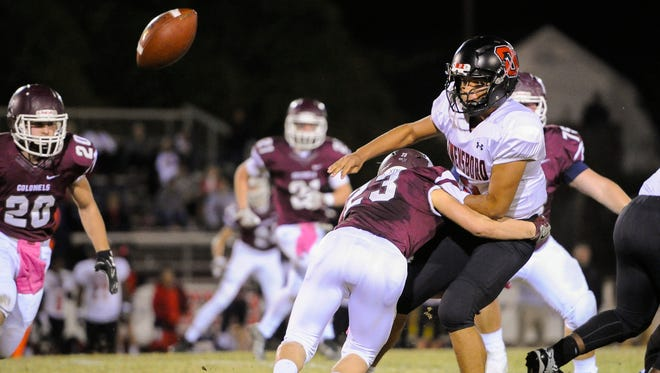 Owensboro's Zach Gross (9) passes the ball before being tackled by Henderson County's Meric-Dean Stinson (23) during their game at Colonel Stadium in Henderson, Friday, Oct. 28, 2016.